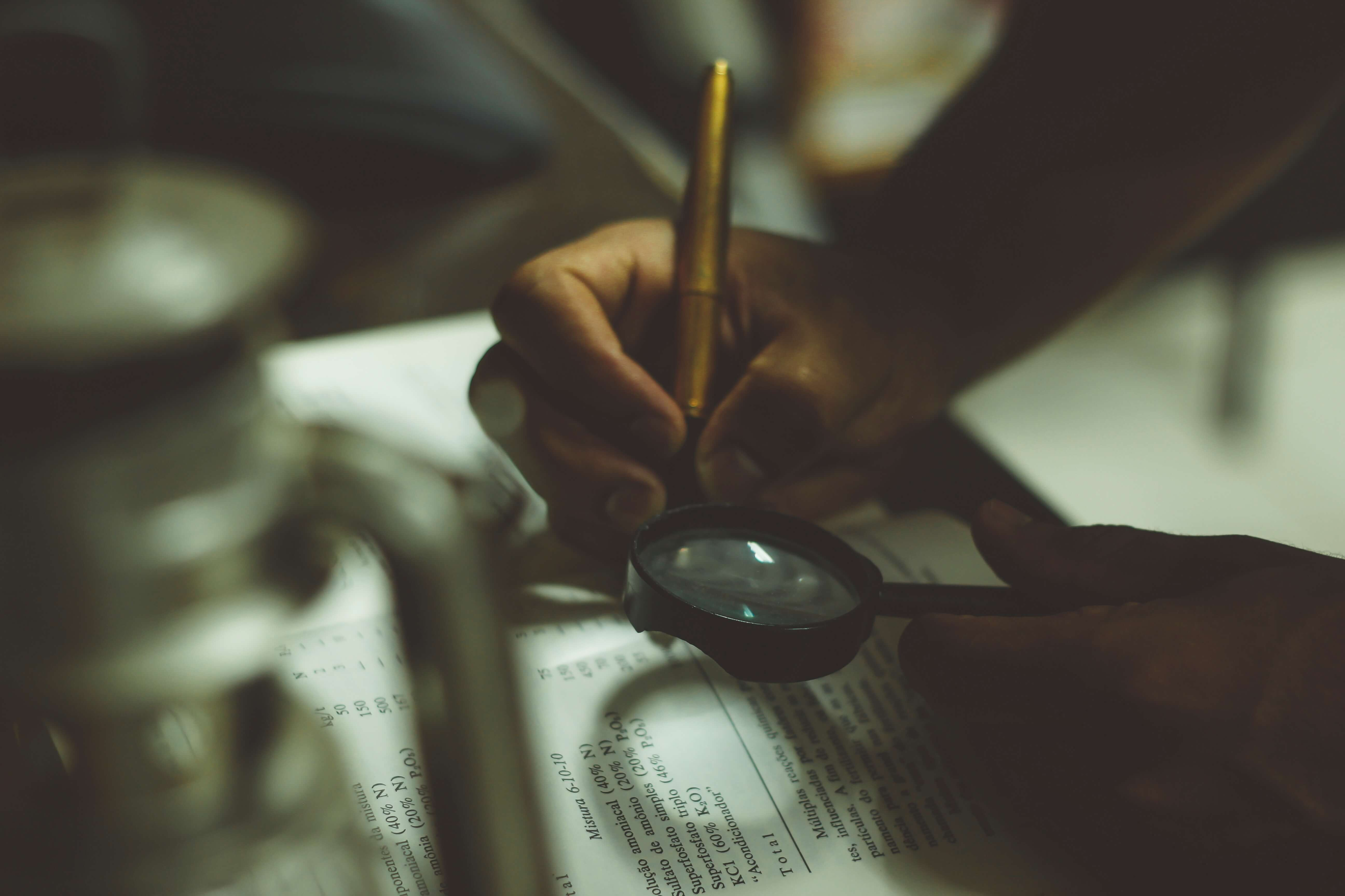 Person using a magnifying glass to read small print and a pen to make notes in a book.