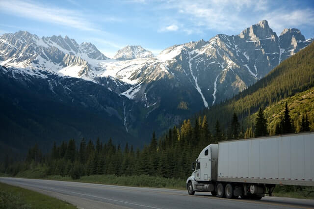 Semi tractor trailer in front of mountains